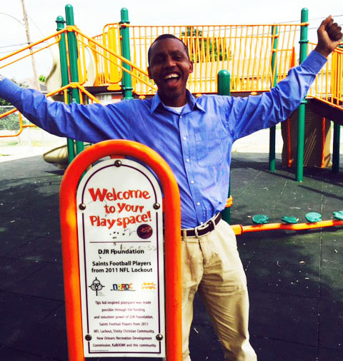 Jarvain celebrating in front of a KaBOOM! playground sign